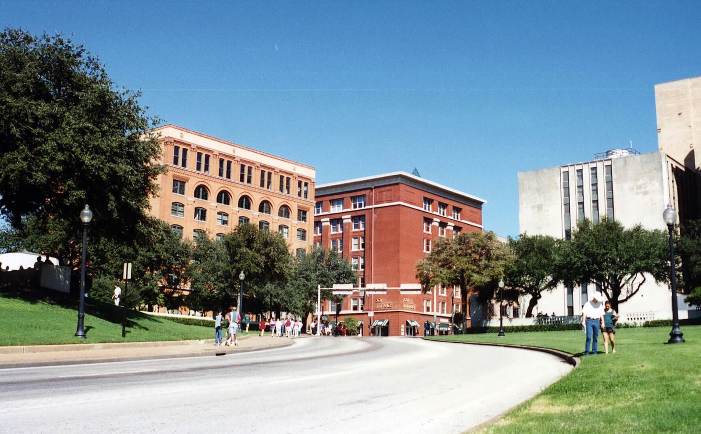 People walking along sidewalk in Dealey Plaza